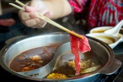 Pinnar tar nötköttskivan in i shabushabukrukan, sund mat arkivbild