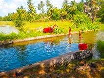 Pinnawella Sri Lanka - Maj 02, 2009: Den tvättande kläderna för lokalt folk i floden Fotografering för Bildbyråer