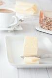 Pinne av smör på den vita plattan Arkivbild