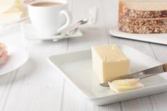 Pinne av smör på den vita plattan Royaltyfri Bild