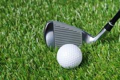 Pinne- och golfbollnärbild mot en bakgrund av grönt gräs arkivbilder