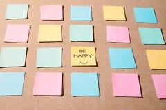Pinneanmärkningspapper med text - Var lycklig på träbakgrund för att påminna din minnesstillebenstil arkivfoto