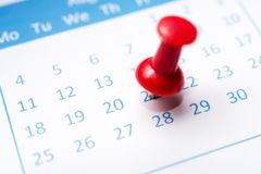 Pinned on calendar. Close up of calendar pinned with thumbtack stock photography