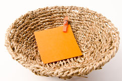 Pinned orange notepad in weave basket Stock Photos