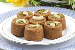 Punjabi Pinni. Pinni is a type of Punjabi and North Indian cuisine dish that is eaten mostly in winters. It is served as a dessert and is made from desi ghee Stock Images
