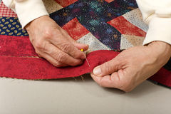 Pinning on a border on a quilt. Quilter pinning a red border on a quilt top Royalty Free Stock Photography