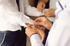 Pinning Cuff Links. Groomsman helping groom to pin cuff links stock photography