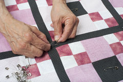 Pinning quilt top border to backing. Quilter pinning quilt top to backing Royalty Free Stock Photos