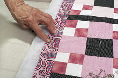 Pinning quilt top border to backing. A quilter pins border through batting and backing Royalty Free Stock Photos