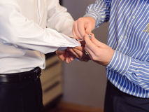 Pinning Sleeve Links. Groomsman helping groom to pin sleeve links stock image
