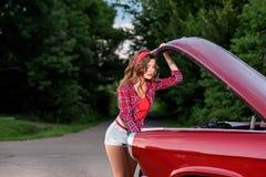 Pino bonito acima da menina que veste a camisa quadriculado vermelha que verifica o motor retro do ` s do carro fotos de stock