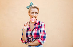 Pino bonito feliz acima da menina que está e que come o pirulito colorido Imagem de Stock