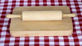 Pino do rolo de madeira em uma placa com o pano de tabela chequered foto de stock