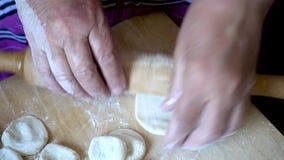 Pino do rolo nas mãos para rolar a massa para bolinhas de massa na mesa de madeira do corte vídeos de arquivo