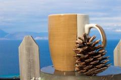 pino e mare della tazza di caffè ai precedenti fotografia stock libera da diritti