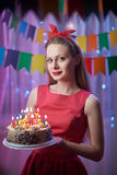 Pino novo bonito do vintage acima da menina do estilo que está no bolo iluminado colorido da terra arrendada da cena com velas Imagem de Stock