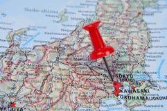Pino vermelho que aponta Tokyo no mapa no atlas Fotografia de Stock