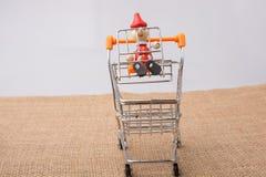 Pinocchio, das auf Einkaufslaufkatze sitzt Lizenzfreie Stockfotografie