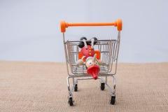 Pinocchio, das auf Einkaufslaufkatze sitzt Stockbilder