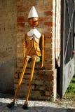 Pinocchio, das an einer Spalte in der Ecke des Schlosses von Strassoldo Friuli (Italien, sitzt) Stockfotos