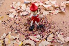 Pinocchio, das unter Bleistiftschnitzeln sitzt Stockfoto