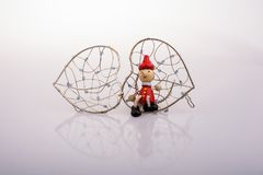 Pinocchio-Puppe, die auf einem Herzen sitzt, formte Käfig Stockfotografie