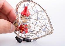 Pinocchio-Puppe, die in einem Herzen sitzt, formte Käfig Stockbild