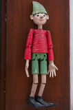 Pinocchio puppet. Hanging on strings in front of wooden door Stock Photography