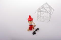 Pinocchio se reposant près d'une maison modèle photos libres de droits