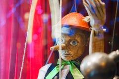 Pinocchio-Spielzeugmarionette gemacht vom hölzernen Hintergrund Lizenzfreie Stockbilder