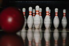 pinos de boliches sujos com a bola vermelha no primeiro plano Imagens de Stock Royalty Free