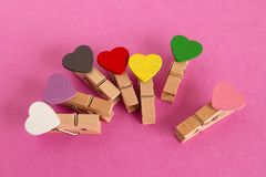 Pinos de madeira com corações coloridos no fundo cor-de-rosa Foto de Stock Royalty Free