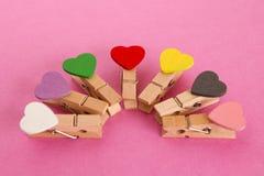 Pinos de madeira com corações coloridos no fundo cor-de-rosa Imagem de Stock