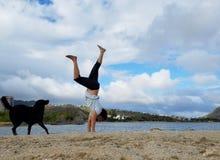 Pinos do homem na praia com o cão preto ao lado dele em Havaí Kai fotografia de stock