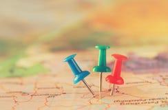 Pinos unidos ao mapa, mostrando o destino do lugar ou do curso Imagem retro do estilo Foco seletivo Imagens de Stock