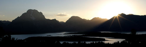 A pinpoint of light squeaks by a mountain range Royalty Free Stock Photos