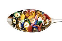 Pins. Spoon full of colorful thumbtacks Stock Photography