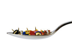 Pins. Spoon full of colorful thumbtacks Royalty Free Stock Images