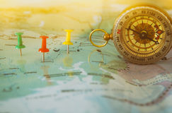 Pins attached to map, showing location or travel destination and old compass. Selective focus Stock Image