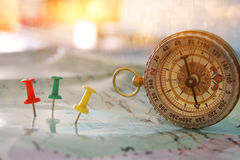 Pins attached to map, showing location or travel destination and old compass. Stock Photos