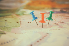 Pins attached to map, showing location or travel destination . retro style image. selective focus. stock photography