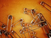 Pins. Of different sizes on orange background with special effect Stock Photos