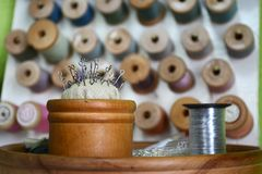 Pins with a round hat in a wooden round box and a coil of metal threads on the background of different threads stock photo