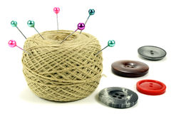 Pins for sewing with the coil of threads and color buttons on a white background Stock Image