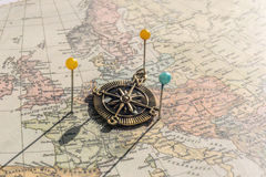 Pins and vintage compass on an old world map Royalty Free Stock Image