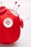 Pins in wool ball with buttons Royalty Free Stock Photo