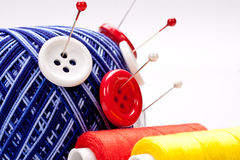 Pins in wool ball with buttons Stock Photography