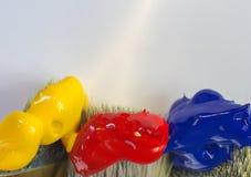 Pinsel des Makro drei mit roter, gelber und blauer Farbe auf einem weißen Hintergrund Platz für Text, für Fahne, für Standort Lizenzfreies Stockfoto