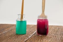 Pinsel mit blauer und roter Farbe tauchten in Wasser ein Stockfotos