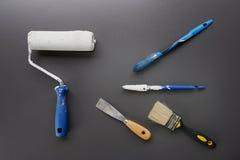 Pinsel, Rolle und Werkzeuge für Hausmalerei auf schwarzem Hintergrund stockbilder
